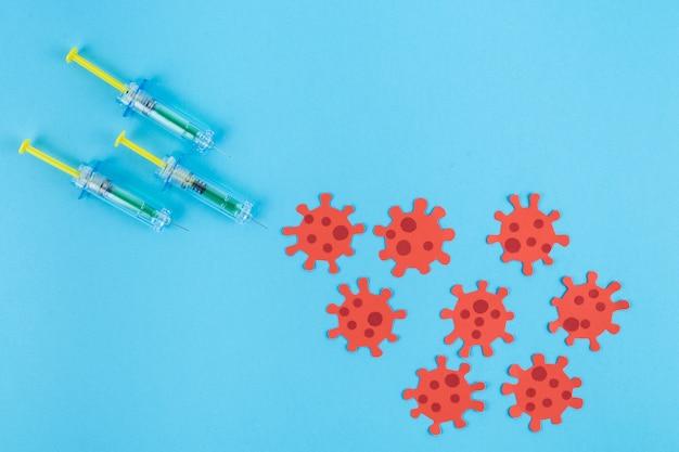 Três seringas picando um grupo de vírus vermelhos