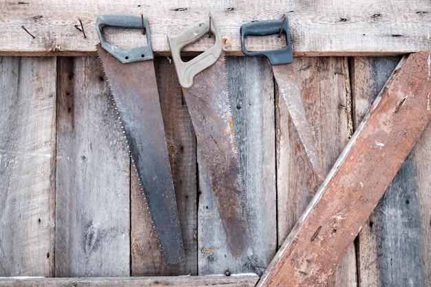 Três serras enferrujadas velhas penduradas na parede de madeira