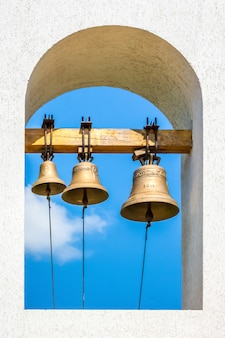 Três sinos na torre do sino da igreja ortodoxa no fundo do céu azul em um dia ensolarado