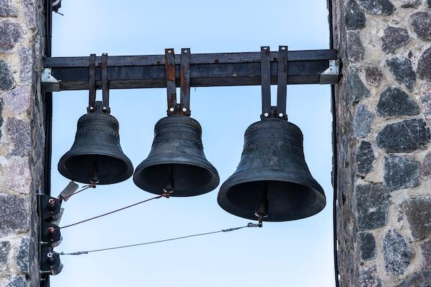 Três sinos pendurados na torre do sino da igreja cristã. foto de alta qualidade