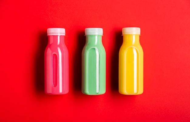 Três smoothies coloridos sobre fundo vermelho