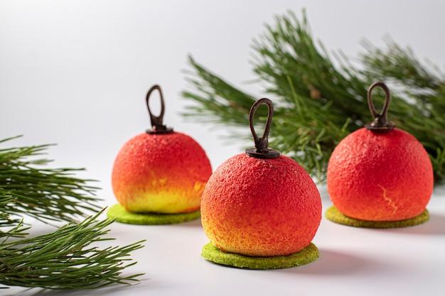 Três sobremesas de mousse em forma de bolas de natal em fundo branco. festa de ano novo. formato horizontal