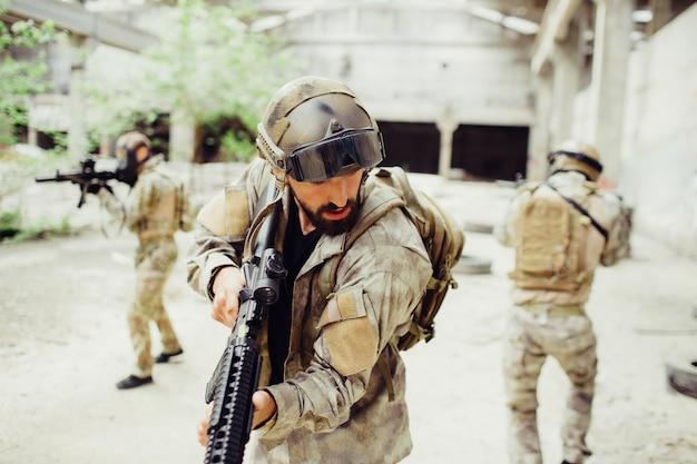 Três soldados estão em pé em um prédio grande e brilhante. eles estão mantendo o silêncio. os homens são muito cuidadosos. eles estão prontos para lutar e se defender. cara na frente está olhando para baixo.