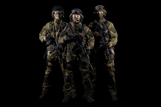 Três soldados uniformizados com uma arma nas mãos olham ameaçadoramente. mídia mista