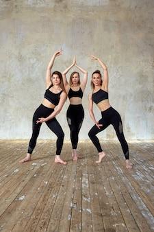 Três sorrindo lindas, garotas de fitness posando em uma sala de fitness.