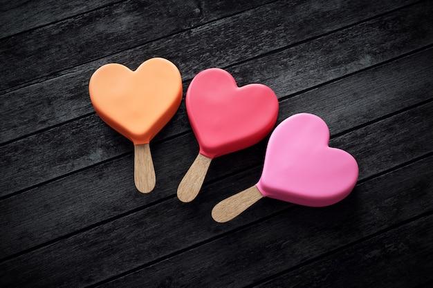 Três sorvetes em forma de coração nas cores rosa