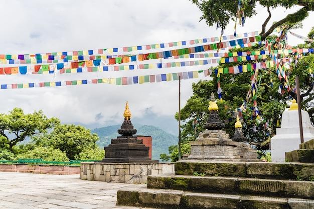 Três stupas e bandeiras coloridas de adoração no templo de swayambhunath na cidade de kathmandu. mosteiro budista.