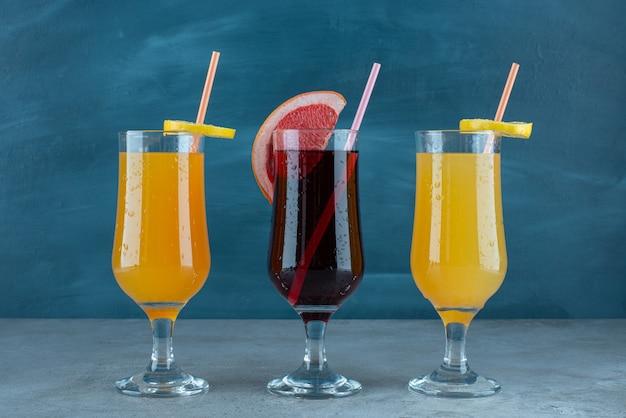 Três sucos diversos em copos de vidro com canudo.