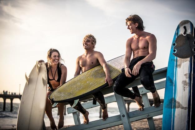 Três surfistas relaxantes na praia depois do esporte
