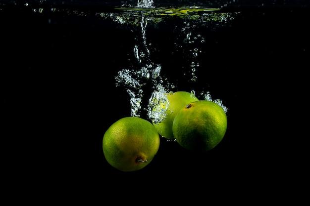 Três tangerinas frescas na água