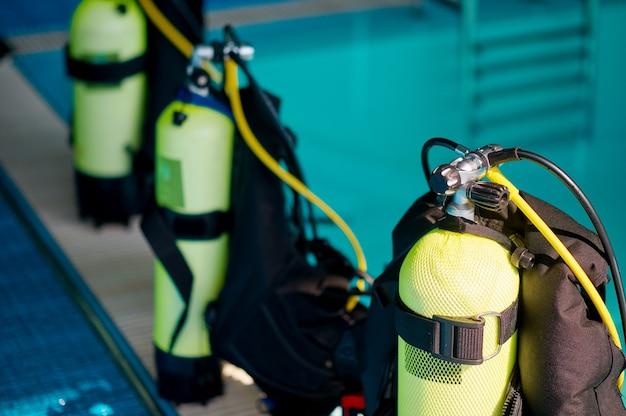 Três tanques de oxigênio ao lado da piscina, equipamento de mergulho