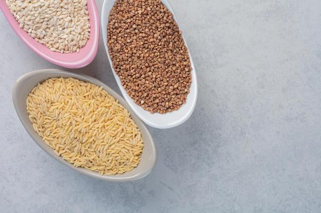Três tigelas com arroz, trigo e trigo sarraceno na superfície de mármore