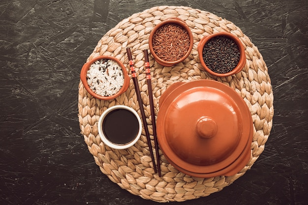 Três tigelas de grãos de arroz cru com molho de soja; pauzinhos no placemat