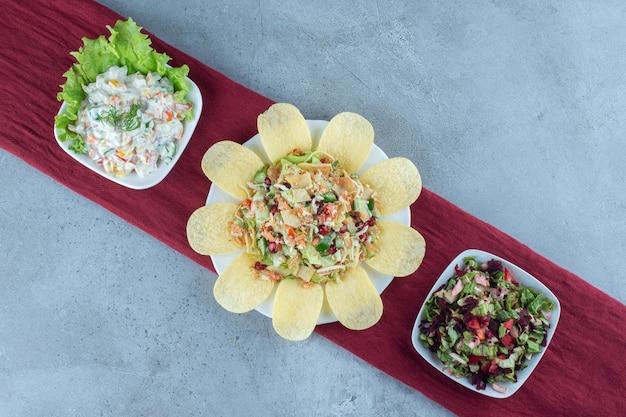 Três tigelas de várias saladas decoradas com folha de alface e batata frita em superfície de mármore