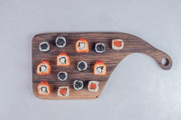 Três tipos clássicos de sushi rola em fundo branco com pauzinhos.