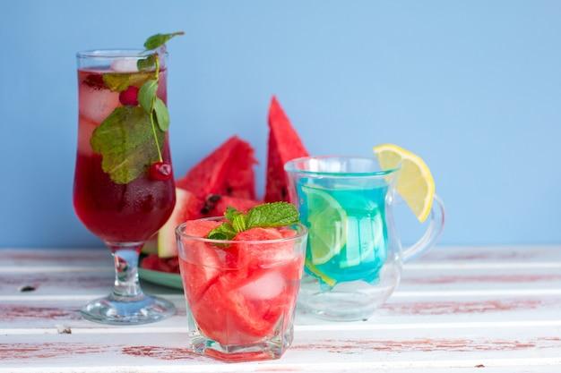 Três tipos de bebidas de frutas e bagas diferentes. cereja, melancia vermelha e azul com coquetéis alcoólicos e não alcoólicos de limão no verão