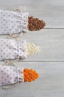 Três tipos de cereais crus, arroz de trigo sarraceno e lentilhas em sacos de lona deitados planos na madeira branca