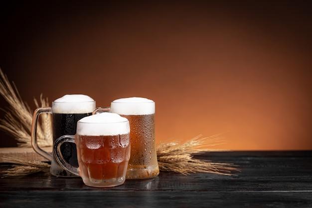 Três tipos de cerveja gelada em jarros e espigas de trigo na base de madeira.