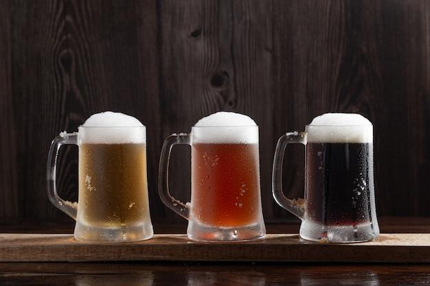 Três tipos de cerveja gelada em jarros na base de madeira.