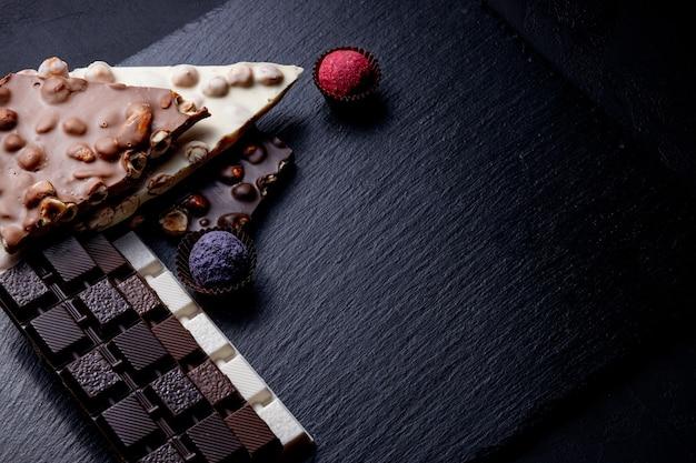 Três tipos de chocolate - preto, leite e branco com chocolates artesanais de luxo em um fundo preto com espaço de cópia.