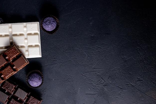 Três tipos de chocolate preto, leite e branco com chocolates artesanais de luxo em um fundo preto