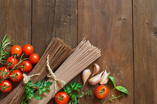 Três tipos de espaguete, tomate e ervas na vista superior da madeira com espaço de cópia