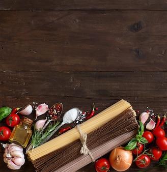 Três tipos de espaguete, vegetais e ervas em uma mesa de madeira