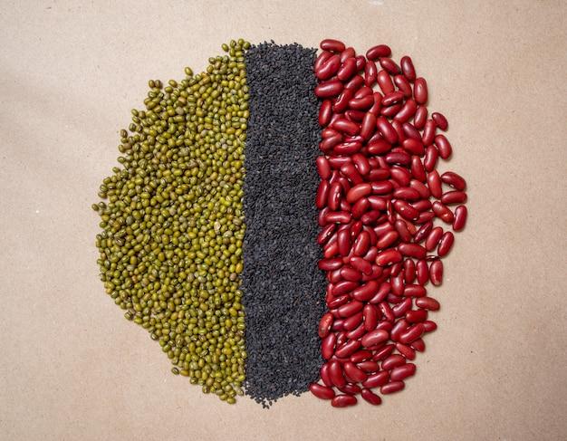 Três tipos de grãos integrais, sementes de gergelim preto, feijão vermelho, feijão verde.