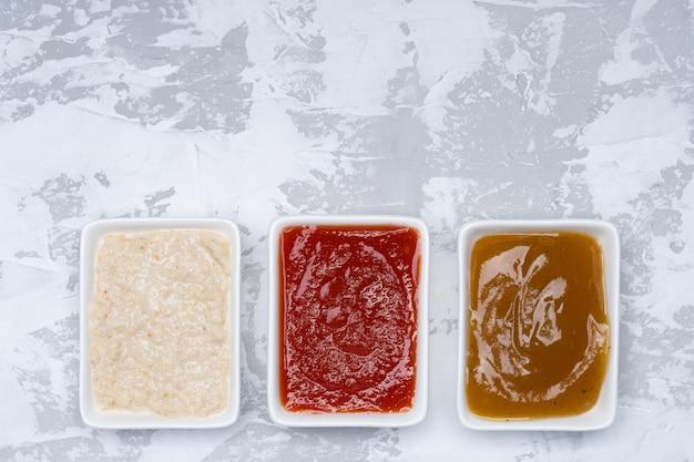 Três tipos de molhos em um fundo de cimento branco