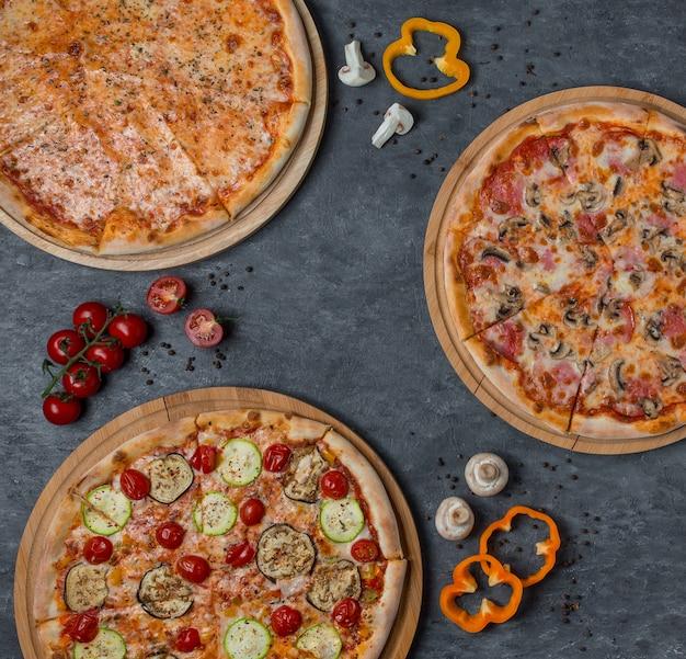 Três tipos de pizza com ingredientes misturados