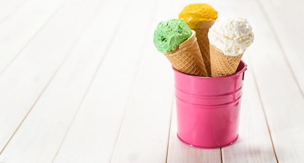 Três tipos de sorvete em cones de waffel