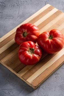 Três tomates da herança na placa de madeira
