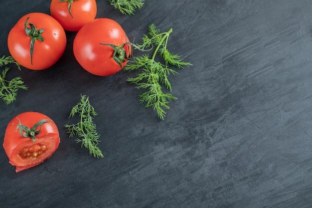 Três tomates frescos com folhas em um fundo escuro.