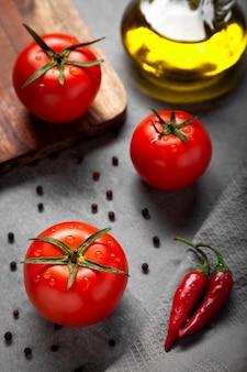 Três tomates maduros vermelhos frescos com gotas, garrafa de azeite, pimenta preta e chili