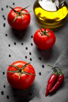 Três tomates vermelhos frescos com gotas, garrafa de azeite, pimenta preta e chili