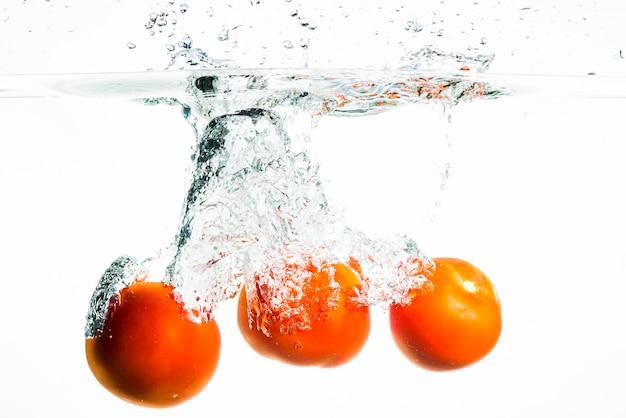 Três tomates vermelhos inteiros chapinhar na água em fundo preto