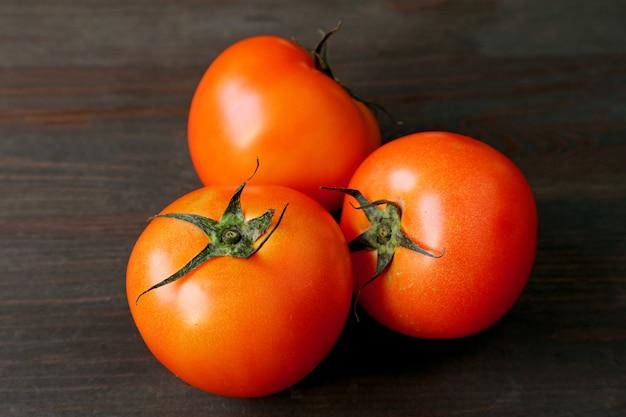 Três tomates vermelhos vibrantes na mesa de madeira marrom escura