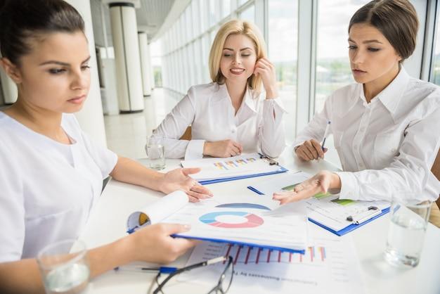 Três trabalhadores de escritório confiantes sentado à mesa.