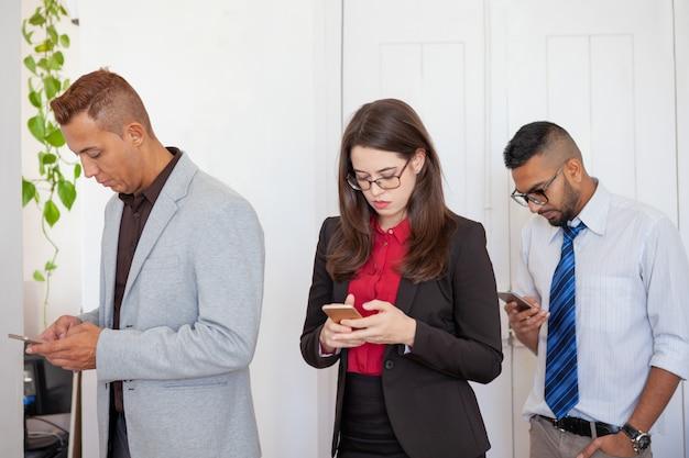 Três trabalhadores de escritório focados em smartphones