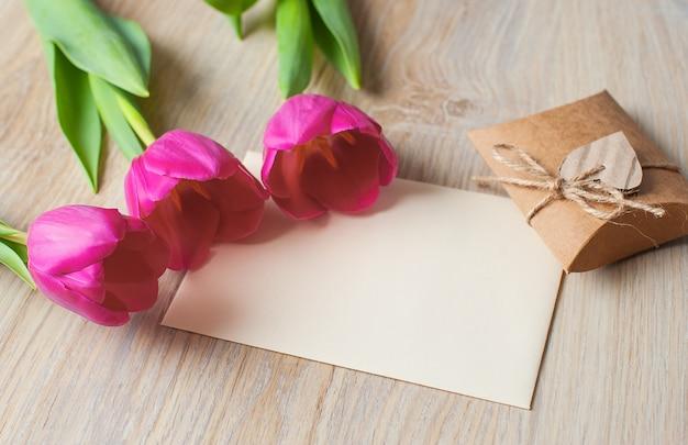 Três tulipas roxas e cartão de felicitações
