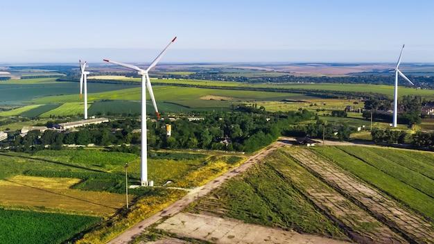Três turbinas eólicas localizadas em um campo