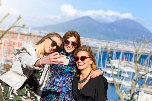 Três turistas fazem uma selfie em frente ao vesúvio.