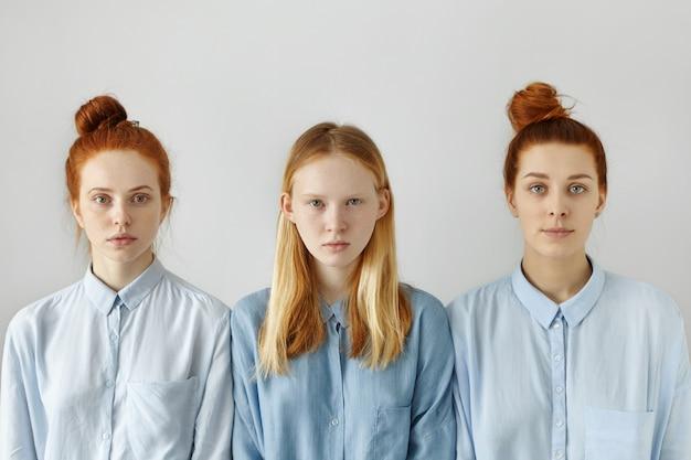 Três universitárias ou irmãs vestidas com camisas posando contra uma parede branca, tendo expressões faciais neutras. menina loira em pé entre duas amigas de cabelos vermelhas