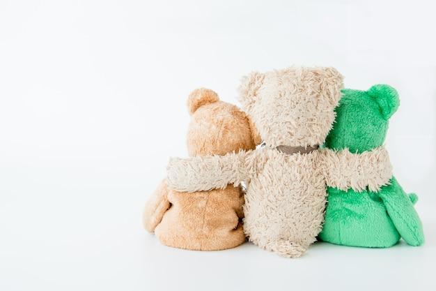 Três ursos de pelúcia segurando em seus braços
