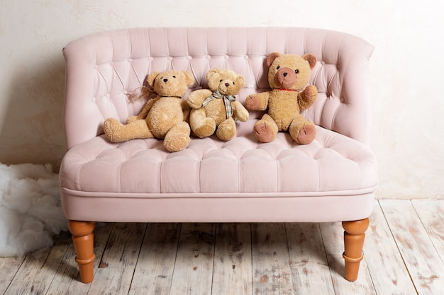 Três ursos de pelúcia sentado no sofá rosa.