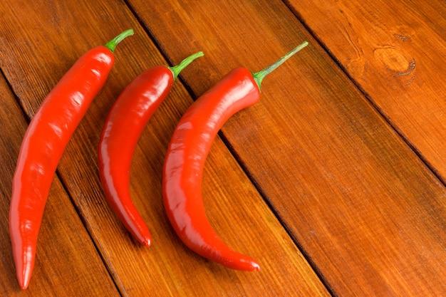 Três vagens de pimenta vermelha repousam à esquerda em um fundo de madeira