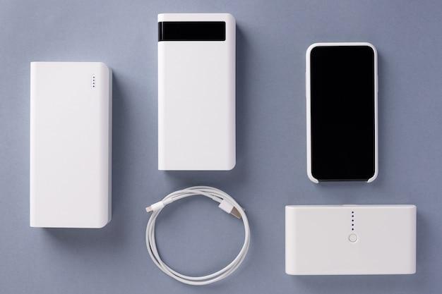 Três vários carregadores de banco de potência, cabos usb e smartphone