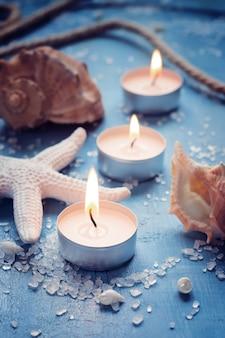 Três velas acesas em uma fileira no fundo de objetos do mar
