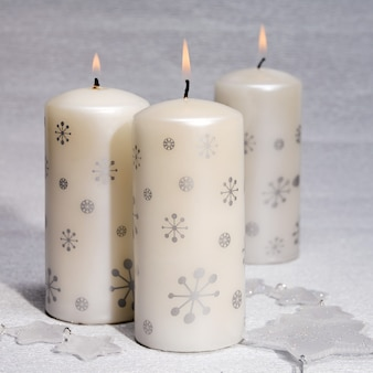 Três velas brancas acesas com estrelas prateadas Foto Premium