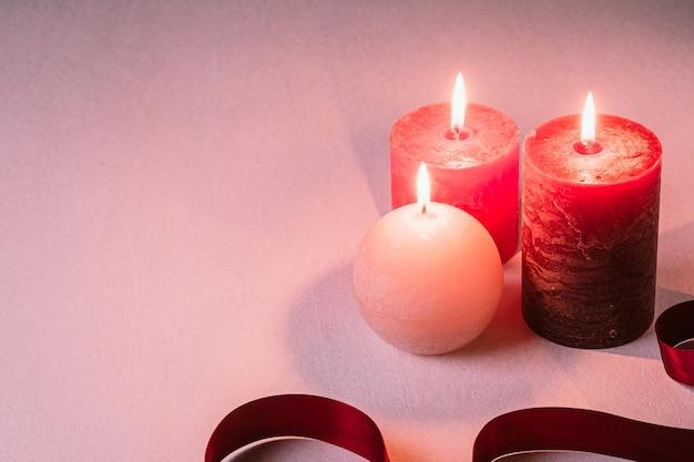 Três velas de chama de cera com fita vermelha no branco